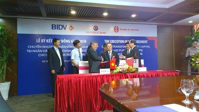 Đại diện BIDV (trái) và VID Public Bank bắt tay trong lễ ký kết chuyển nhượng vốn góp vào tháng 7-2014