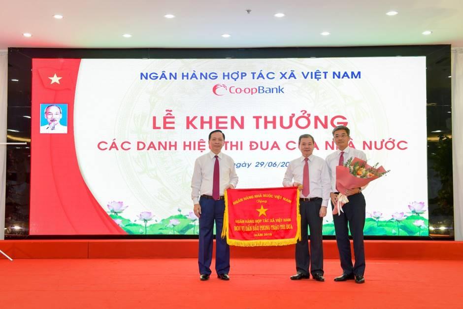 Phó Thống đốc Thường trực NHNN Đào Minh Tú trao Cờ thi đua của NHNN cho NHHT